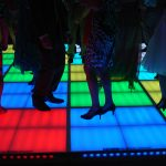 Legs and feet dancing on multicolored LED dancefloor